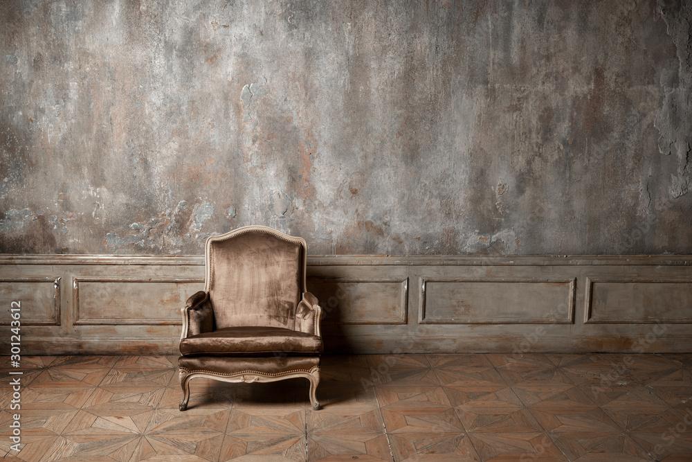 Fototapeta old armchair against a vintage wall
