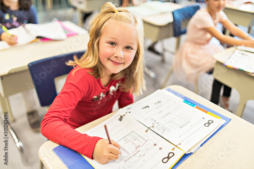 Obraz education and school concept little student girl studying at school - fototapety do salonu