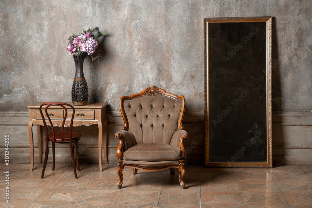 Fototapeta old chair, a mirror and a table with flowers on background of vintage wall