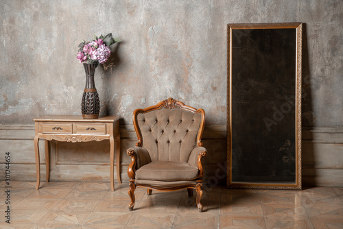 old chair, a mirror and a table with flowers on background of vintage wall Canvas-taulu
