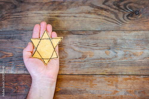 Fotografía Male hand and star of David on a wooden board background