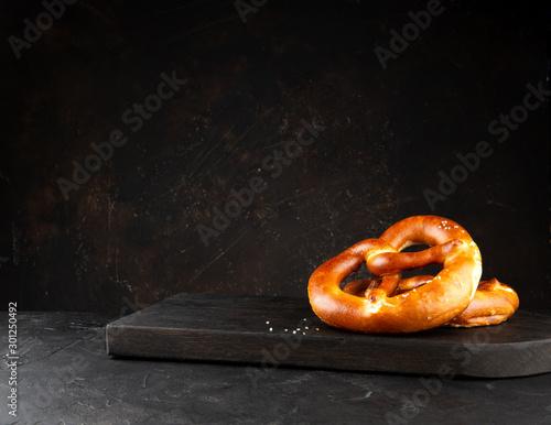Fototapeta Pretzels with salt on a wooden black board on dark background