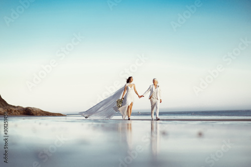 Lesbian women just married holding for their hands walk on the beach near the ocean