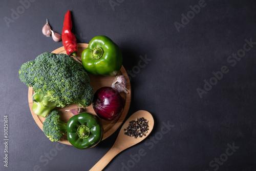 Fotografía  Fresh vegetables, green broccoli, peppers, garlic and onion on a black board
