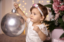 Cute Toddler Girl Playing With A Big Silver Ball To Decorate A Christmas Tree