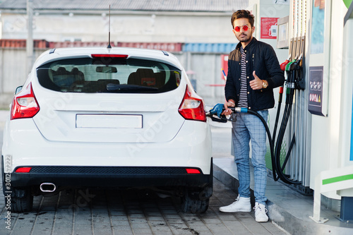 Photo South asian man or indian male refueling his white car on gas station