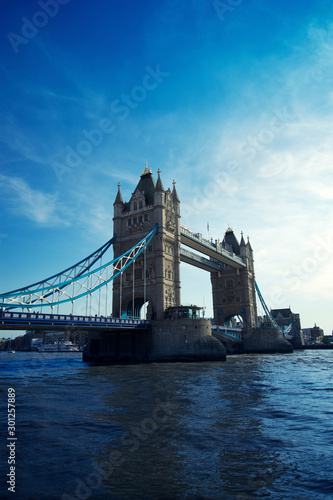 London's Tower Bridge standing in timeless elegance above the flowing River Thames under blue sky