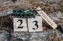 February 23. Holiday Card With Date Of The 23th February On Wooden Calendar And Model Of Toy Tank. Men's Day In Russia, Belarus, Tajikistan And Kyrgyzstan. Fatherland Defender Day.