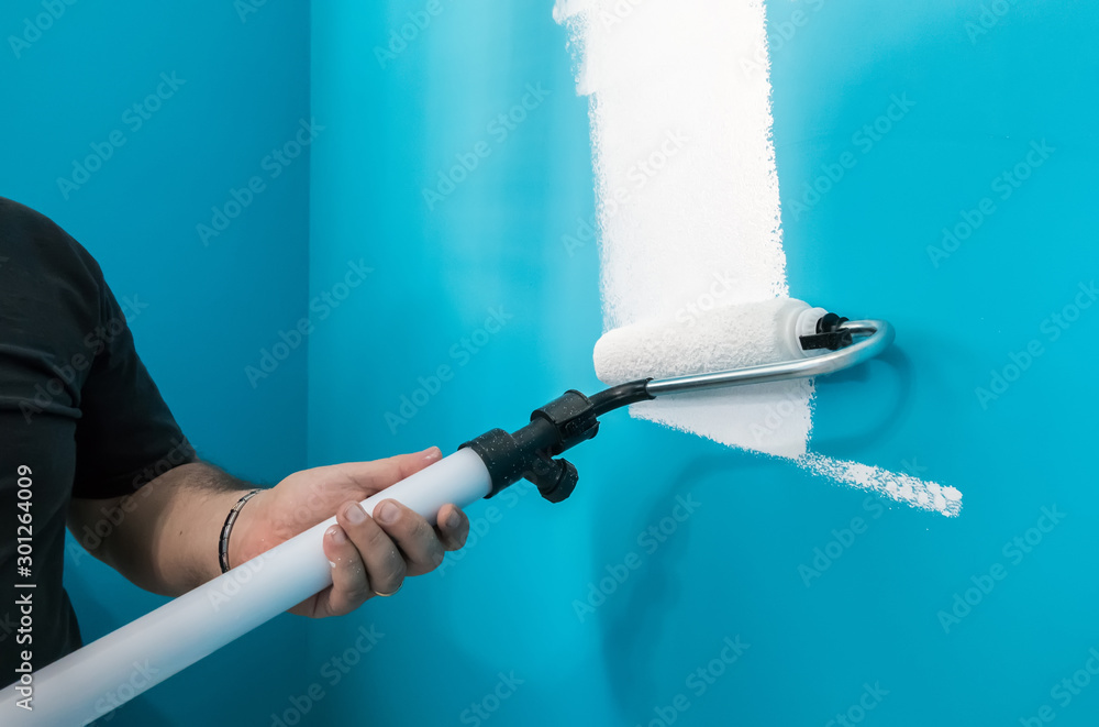 Fototapety, obrazy: Young man painting wall with paint roller. Man at work concept