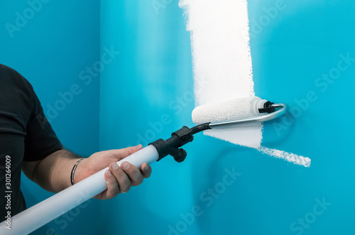 Fotografía  Young man painting wall with paint roller. Man at work concept