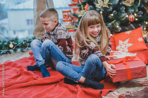 Greedy sister has stolen brother's present and looks at the camera with cunning face expression, while ffended boy is sitting near her looking upset Tapéta, Fotótapéta