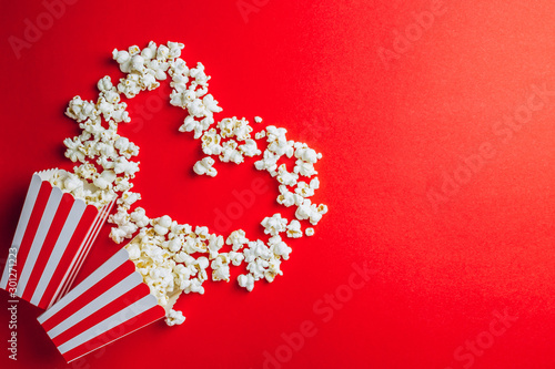 Fototapeta Tasty salted popcorn in striped cardboard box on red background. Top view. Flat lay. Copy space. Heart shape, Valentines day obraz
