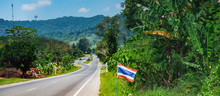 Asphalt Road With Thai Flags In A Row, Tropical Forest And Mountains Near Khao Sok National Park, Thailand. It Is The Main Tourist Route To The Andaman Sea - Phuket Island And Khao Lak.