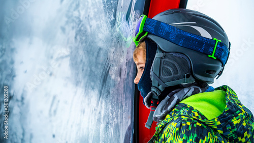 Cute, young boy snowboarding, in the chairlift on the way to the mountain peak, looking trough the icy window Wallpaper Mural
