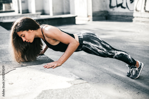 Fototapeta Beautiful sport fitness girl in sportswear doing fitness exercise in the street ,outdoor sports. Urban style. obraz na płótnie