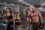 A bearded man and a group of women are engaged in the gym with dumbbells. The bodybuilder does exercises for biceps and triceps. A lesson from a personal trainer.