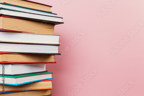A simple composition of many hardback books, raw books on a wooden table and a p Fototapet