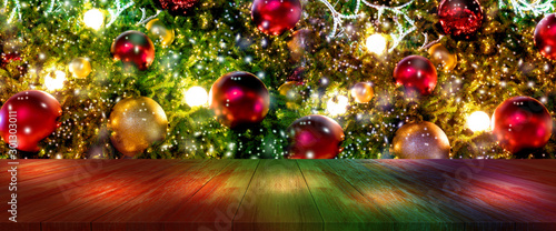 Poster Trees top wood desk with christmas tree and red ball hanging blur background,wooden table