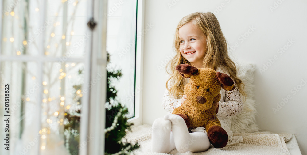 Fototapety, obrazy: little girl with a plush deer sitting on the window. A child looks out the window and is waiting for Christmas, Santa Claus