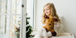 canvas print picture - little girl with a plush deer sitting on the window. A child looks out the window and is waiting for Christmas, Santa Claus