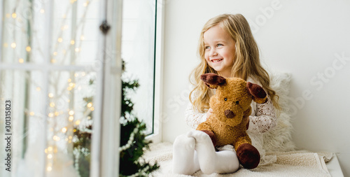 Fototapeta little girl with a plush deer sitting on the window. A child looks out the window and is waiting for Christmas, Santa Claus obraz