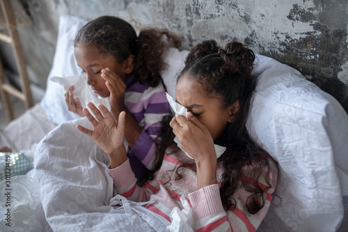 Valokuva Two sisters lying in bed and sneezing after catching flu