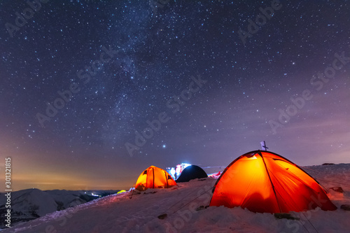 Spoed Foto op Canvas Kamperen Great bright campsite with colorful tourist tents, on top in the Ukrainian Carpathian Mountains, at night with views of the stars and the Milky Way