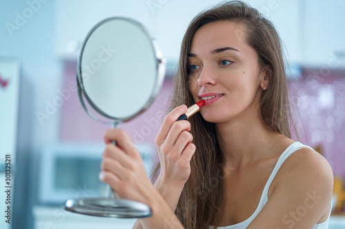 Obraz Beautiful attractive happy smiling brunette woman paints lips with red lipstick using a small round mirror during home makeup in the morning - fototapety do salonu
