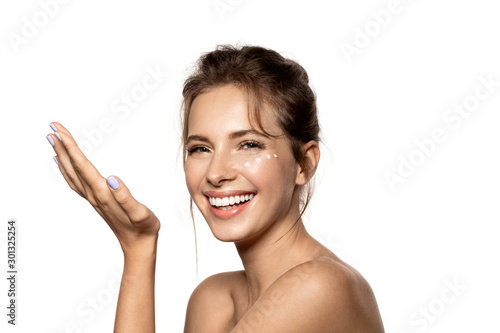 Fotomural  Portrait of beautiful woman using cream for facial skin
