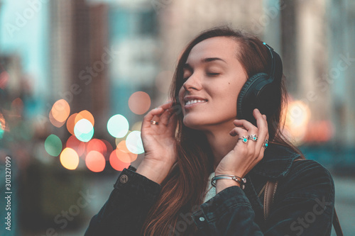 Young happy stylish trendy casual hipster woman teenager listening to music on a wireless headphone while walking around the city Wallpaper Mural