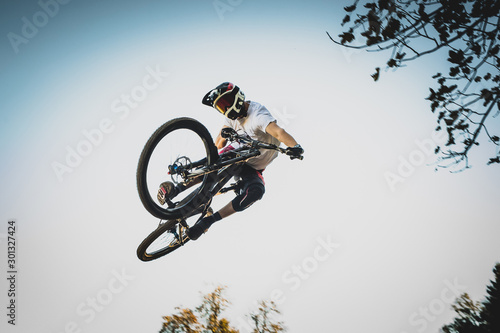 Stampa su Tela Mountain biker jumping over a dirt jump.