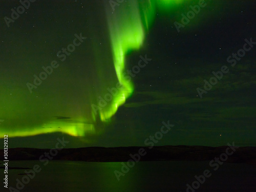 Photo  Northern lights over the lake and hills