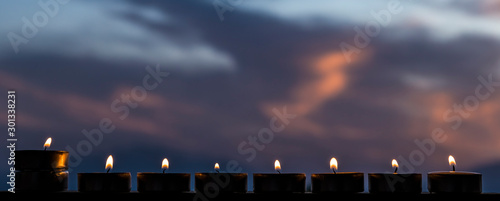 Lights of candles against blurred dramatic sky