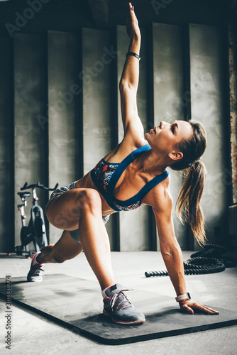 Fotomural  Young athletic woman warming up before workout in the gym