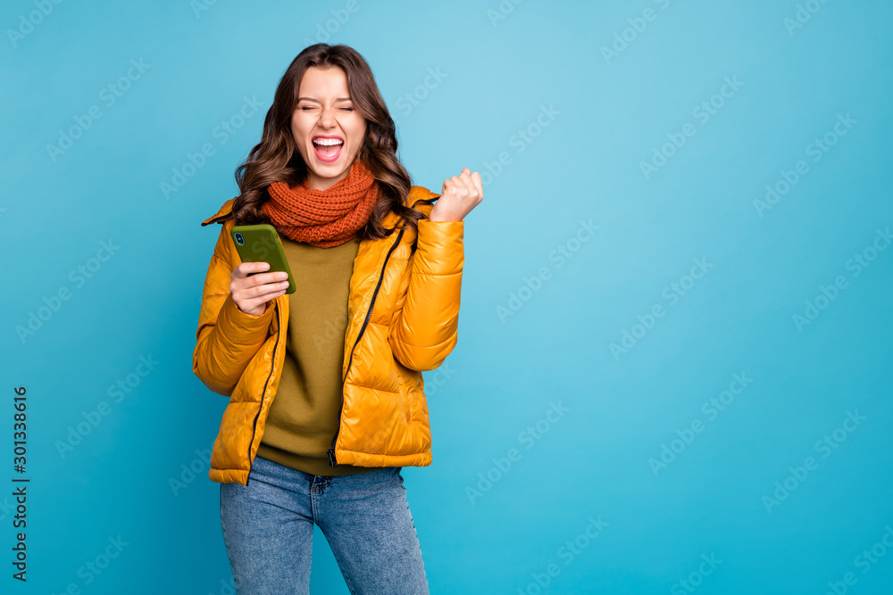 Fototapeta Photo of crazy millennial lady holding telephone astonished big number of new subscribers wear stylish windbreaker jeans scarf pullover isolated blue color background