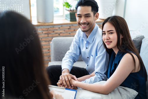 Fototapety, obrazy: Asian couple patients sitting on sofa explaining and consulting problem to professional psychologist female, feeling happy after get some advice and can solve problem. Psychology consultant concept.