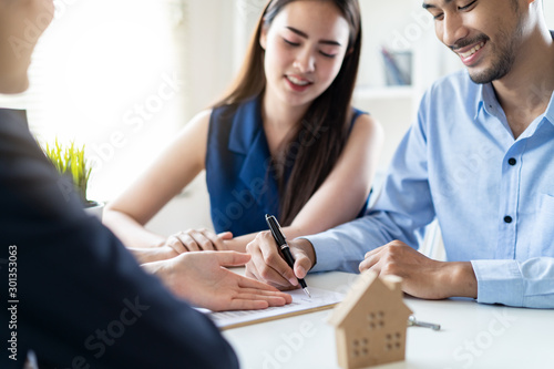 Fotografía  Young Asian couple making contract with house sale agency