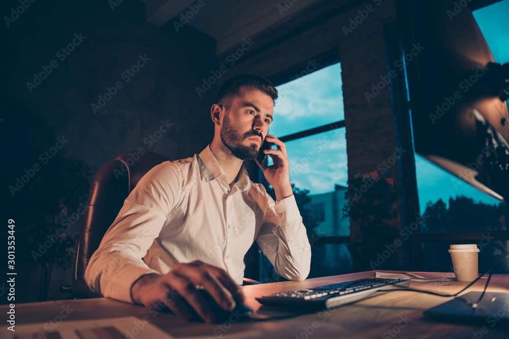 Fototapeta Profile side photo of concentrated collar worker sit table desk work on his pc speak through smartphone want solve job problems to finish research strategy in dark evening loft wearing white shirt