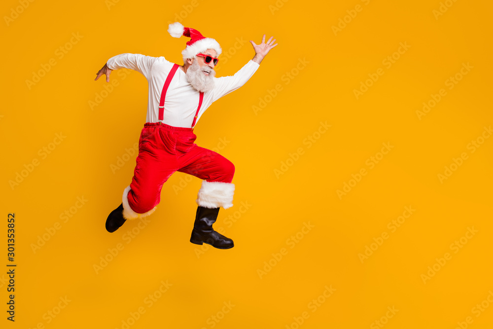 Fototapeta Full body profile side photo of crazy funky grey hair bearded grandfather hipster in red hat jump run enjoy x-mas time party wear black boots isolated yellow color background