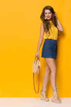 Young Woman In Jeans Mini Skirt And Wedges Is Posng WIth Braided Straw Round Purse