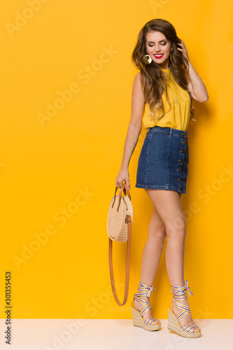 Young Woman In Jeans Mini Skirt And Wedges Is Posng WIth Braided Straw Round Purse Wall mural