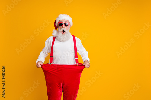 Papiers peints Ecole de Danse Portrait of crazy funky white bearded grandfather in santa claus hat hold big size trousers lose weight belly x-mas time show dieting effect isolated yellow color background