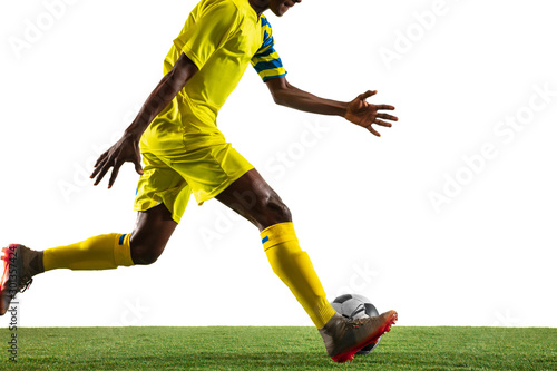 plakat Professional african-american football or soccer player of yellow team in motion isolated on white studio background. Fit man in action, excitement, emotional moment. Concept of movement at gameplay.