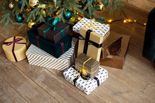 Christmas Gift Boxes On A Wooden Floor Near A Christmas Tree And A Green Sofa