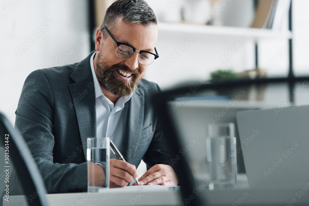 Fototapeta handsome businessman in formal wear and glasses writing with pen in office