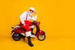 canvas print picture - Full body photo of funny santa aged man in festive mood ready for x-mas theme party sitting on vintage bike wear sun specs pants cap shirt boots isolated yellow color background