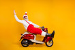 canvas print picture - Full body photo of funny white hair santa in festive mood riding x-mas theme party by bike wear stylish sun specs trousers cap shirt boots isolated yellow color background