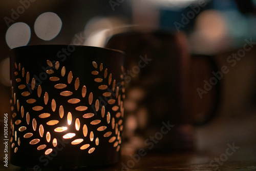 Photo  Very nice patterned in leaves container for candle inside warm and cozy pub duri