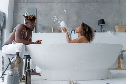 Canvas Print Cute young woman taking bath and having fun with her boyfriend