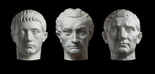 Three Gypsum Copy Of Ancient Statue Heads Isolated On A Black Background. Plaster Sculpture Mans Faces.